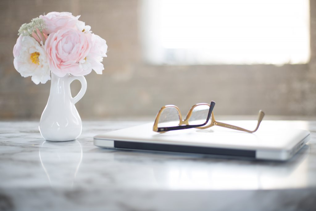 laptop with glasses and flowers in vase on a table